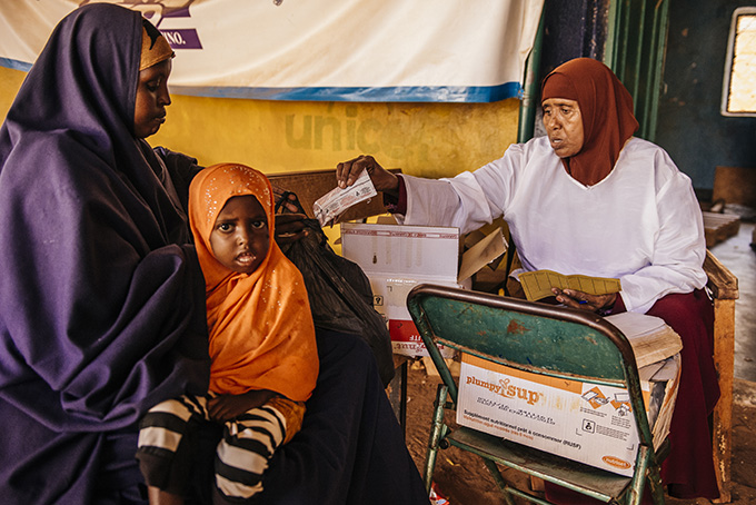 Idle Abdi Mohammed is given her weekly supply of Plumpy Sup for her daughter Zaynab by the nutritionist at Bula Hawa MCH. Credit: Amunga Eshuchi/Trocaire